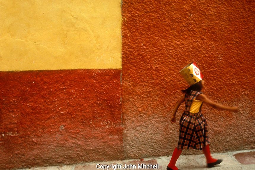 Girl wearing a party hat striding down a street in San Miguel de Allende, Mexico