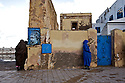 Women in the coastal city of Essaouira stand guard against the cold.