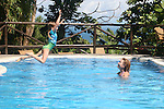 Central America, Costa Rica, Osa. Child plunges into pool at Lapa Rios Eco-Resort.