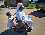 Jennifer Mhlanga suffered a spinal injury in a bus accident, and today uses a wheelchair to get around Harare, Zimbabwe. Here she moves along a street in her neighborhood with help from her three-year old granddaughter, Tariro Bvumakurehwa. Mhlanga's wheelchair, which was carefully fitted to her individual needs, was provided by the Jairos Jiri Association with support from CBM-US.