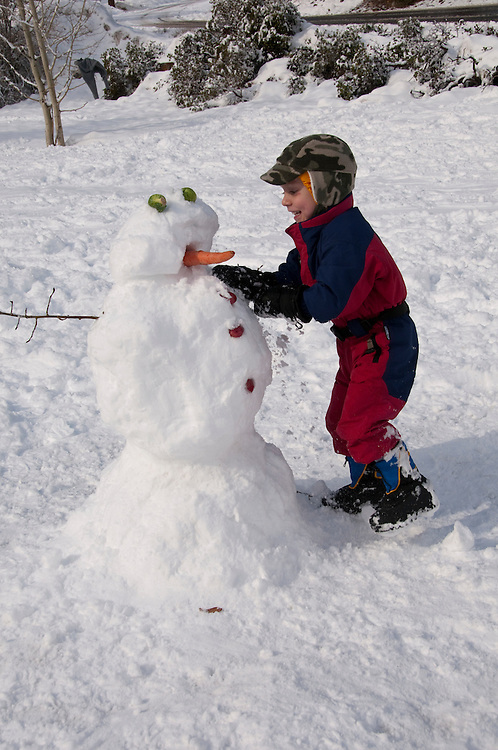 California, Lake Tahoe: Child makes a snow man at  North Lake Tahoe Regional Park.  Photo copyright Lee Foster.  Photo # cataho107585