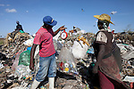 13 february 2013 - Dandora dumpsite, Nairobi, Kenya - A boy weighs recyclables on a scale in Dandora Dumpsite, one of the largest and most toxic in Africa. Located near slums in the east of the Kenyan capital Nairobi, the open dump site was created in 1975 and covers 30 acres. The site receives 2,000 tonnes of unfiltered garbage daily, including hazardous chemical and hospital wastes. It is a source of survival for many people living in the surrounding slums, however it also harms children and adults' health in the area and pollutes the Kenyan capital. Photo credit: Benedicte Desrus