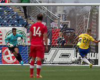 Brazilian player Gabriella Demoiser (21) scores on penalty kick even though Canadian goalkeeper Karina LeBlanc (1) guessed correctly. In an international friendly, Canada defeated Brasil, 2-1, at Gillette Stadium on March 24, 2012.