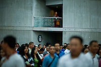 A TIbetan Buddhist is seen on second floor as Dalai Lama supporters exit the Javitz Center while Shugden Community members and American tibetans take part in a protest regarding religious intolerance against their Buddhist community while the Dalai Lama visits New York. 07.09.2015. Eduardo MunozAlvarez/VIEWpress.