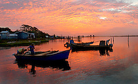 Eastpoint, FL. 7/27/06-Oystermen ready their boats for a day of work on Apalachicola Bay as the sun ignites the sky over Eastpoint. COLIN HACKLEY PHOTO