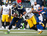 Russell Wilson #3 of the Seattle Seahawks evades a tackle on the run from Lawrence Timmons #94 of the Pittsburgh Steelers in the second half during the game at CenturyLink Field on November 29, 2015 in Seattle, Washington. (Photo by Jared Wickerham/DKPittsburghSports)
