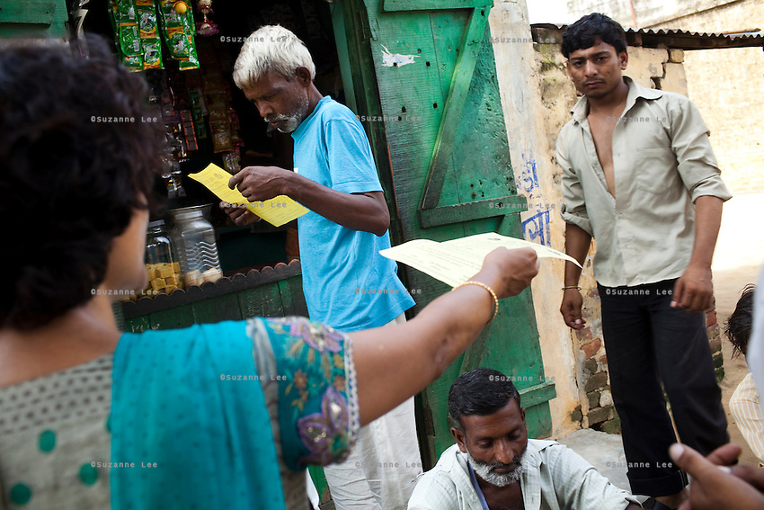 A shopkeeper (man in blue) is interested in NSV after reading the leaflets. Jagroshan Sharma (aged 36, unseen) approaches random villagers from Shahpurjat village with Dr. Meenal Mehta (lady in blue), who is in charge of the USAID NSV projects in Ghaziabad, Uttar Pradesh, India. After doing NSV himself, he has been a star link worker introducing about 5 NSV cases per month since he started working part time under the tutelage of Dr Mehta. Jagroshan had chosen to do a non-scalpel vasectomy (NSV) for many reasons. He wanted to be an equal partner in the relationship, knew that NSV was less complicated and will not put his wife through numerous problems, and wants his two children to do well in life and study in English medium schools despite his modest earnings. Photo by Suzanne Lee / Panos London