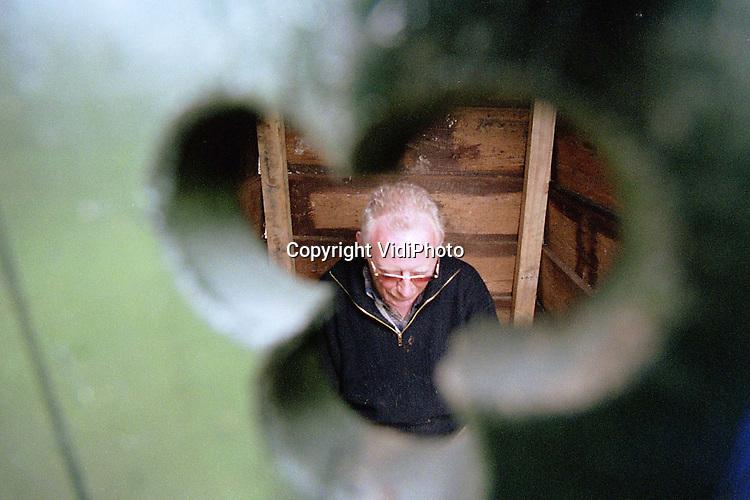"""Foto: VidiPhoto..GROOT-AMMERS - Het ooievaarsdorp Het Liesvelt in Groot-Ammers heeft er een nieuwe attractie bij: een originele kakdoos uit grootmoederstijd. Bedenker .en bouwer is de gepensioneerde bouwvakker Pieter de Jong. Van oud materiaal vervaardigde De Jong in een week tijd een """"gemak, zoals hij dat in het begin van zijn loopbaan ook deed. Het is de bedoeling dat het historisch toilet ook door bezoekers gebruikt gaan worden. Foto: De Jong mocht de kakdoos maandag als eerste uitproberen."""