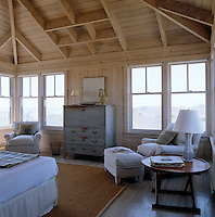 This simply furnished pine-clad bedroom has windows on three sides which look out over the dunes and the sea beyond