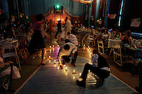Family members light candles to form a heart or circle of love for the wedding reception.