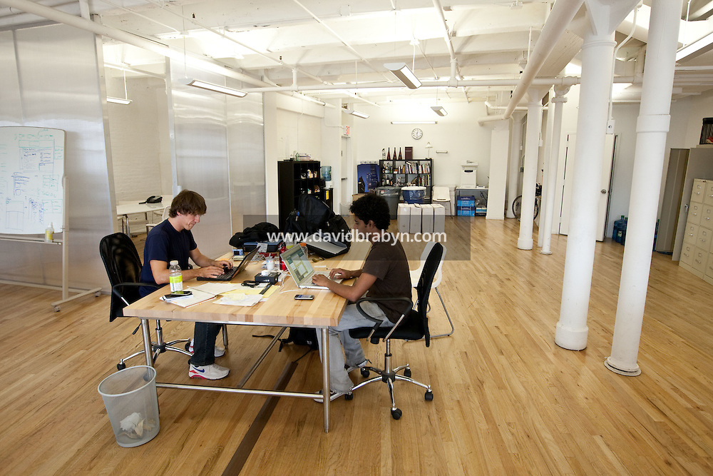 "Dennis Crowley (L) and Naveen Selvadurai, co-founders of social media website Foursquare, work at their desks in their shared office in New York, USA, 5 August 2009. Foursquare, which allows users to stay connected to friends and explore a city, has been dubbed ""the next Twitter"" by an influential tech blog."