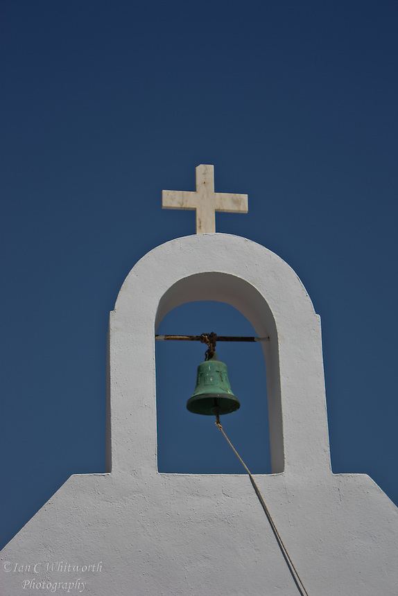 View of a white church's bell under the cross at Mykonos in Greece