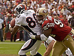 San Francisco 49ers defensive tackle Dana Stubblefield (94) tackles Denver Broncos wide receiver Rod Smith (80) on Sunday, September 15, 2002, in San Francisco, California. The Broncos defeated the 49ers 24-14.
