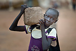 A girl carries a rock that she will use for seating in a school in the Ajuong Thok Refugee Camp in South Sudan. Situated in northern Unity State, the camp hosts thousands of refugees from the Nuba Mountains, located across the nearby border with Sudan. The Lutheran World Federation, a member of the ACT Alliance, provides a variety of services in the camp, including support for children's education.
