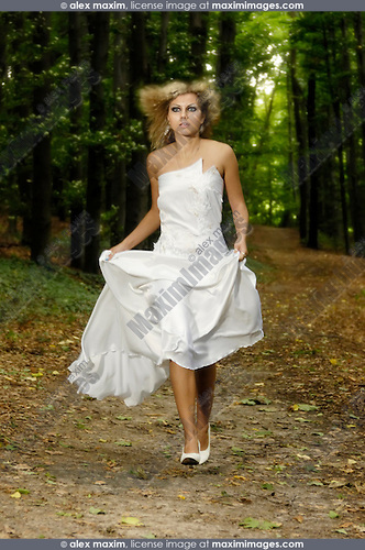 Stock photo of a Young beautiful bride in a white wedding dress running by a forest road Vertical Emotional artistic conceptual portrait