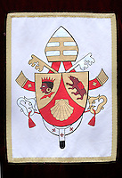 "The coat of arms of Pope Benedict XVI.The coat of arms of Pope Benedict XVI was designed by then Archbishop Andrea Cordero Lanza di Montezemolo (who later was created a Cardinal) soon after the papal election. Benedict's coat of arms has omitted the papal tiara, which traditionally appears in the background to designate the Pope's position as a worldly ruler like a king, replacing it with a simple mitre, emphasising his spiritual authority.[142]  . .Escutcheon Gules, chape in or, with the scallop shell of the second; the dexter chape with a moor's head in natural colour, crowned and collared of the first, the sinister chape a bear trippant in natural colour, carrying a pack gules belted sable . .Symbolism Scallop shell: The symbolism of the scallop shell is multiple, one of the meanings is thought to represent Saint Augustine. While a doctoral candidate in 1953, Fr. Joseph Ratzinger wrote his dissertation on The People of God and the House of God in Augustine's Teaching is always about the Church, and therefore has a personal connection with the thought of this great Doctor of the Church..Moor of Freising: The Moor's head is an heraldic charge associated with Freising, Germany..Corbinian's bear: A legend states that while travelling to Rome, Saint Corbinian's pack horse was killed by a bear. He commanded the bear to carry the load. Once he arrived, he released it from his service, and it returned to Bavaria. The implication is that ""Christianity tamed and domesticated the ferocity of paganism and thus laid the foundations for a great civilisation in the Duchy of Bavaria."" At the same time, Corbinian's bear, as God's beast of burden, symbolises the weight of office that Benedict now carries. ."