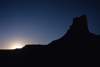 The sun is poised on the horizon, just lighting up a lone butte in Canyonlands National Park, Utah.