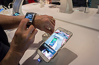 A visitor tries out Samsung products, including their smart watches, in a Samsung pop-up shop in Soho in New York on the Galaxy Note 4 phablet's release date, Friday, October 17, 2014. Samsung released the new Galaxy Note 4 today going head to head with the Apple iPhone 6 Plus in what is being called the phablet wars. (© Richard B. Levine)