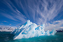 Small iceberg drifting in fiord, June, cirrus clouds, Svalbard, Norway