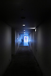 person standing in the strong light of the door opening at end of a long hall