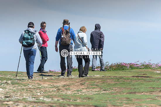 A group of walkers on East Pentire Headland in Newquay, Cornwall.