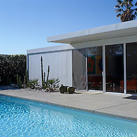 Sliding glass doors lead from the living room onto the swimming pool terrace