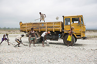 India – West Bengal: Workers loading crushed stones and pebbles on a truck along the Diana riverbed at Red Bank Tea Estate, in the Dooars region. The garden, which houses 888 workers out of a population of 5,000 people, has been closed since 2013. With no more income, food rations and health services, its workers resorted to stonecrushing in order to survive.