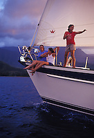 Woman and girls dancing on bow of a 48 foot yacht sailing at sunset in Hanalei Bay, North Shore of Kauai