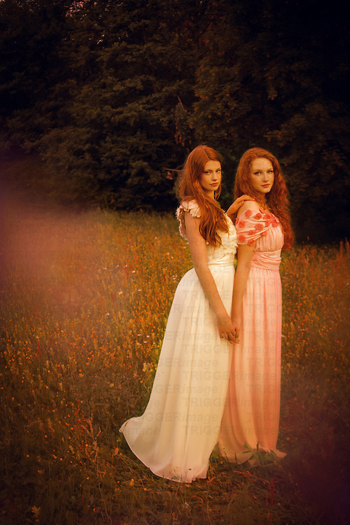 Two girl in pastel gowns standing outsdoors in spring and holding hands.