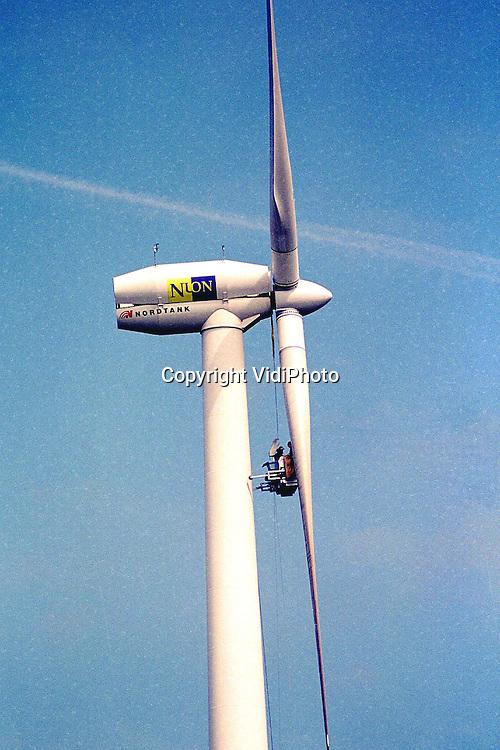 Foto: VidiPhoto..LELYSTAD - Technici van de energiebedrijf NUON repareren vrijdag een windmolen langs het IJsselemeer/A6. Langs de route staan tientallen windmolens die voor schone energie zorgen. De plaatsing van nieuwe windmolens roept echter steeds meer weerstand op. Zo wil de provincie Friesland ze niet meer op het platteland en zijn Milieufederatie en Vogelbescherming tegen nieuwe windmolens in en rond het IJsselmeer, met name in de buurt van wiedevogelgebieden.