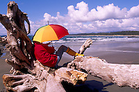 Hiker with Umbrella resting on a Driftwood Tree Trunk Log on Wickaninnish Beach, in Pacific Rim National Park Reserve, on the West Coast of Vancouver Island, British Columbia, Canada (Model Released)