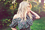Close up of young woman with blonde hair standing alone outdoors in garden