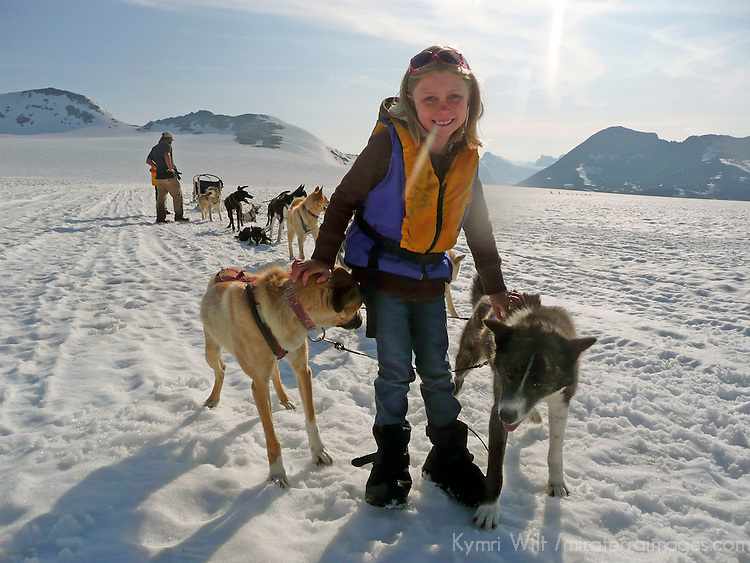 "North America, USA, Alaska, Skagway. Young girl enjoys meeting the dogs and puppies on a ""Glacier Dog-Sledding"" shore excursion in Alaska."