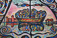 Section of the Berlin Wall depicting a detail of people crowded onto a boat from the painting Wir Sind Ein Volk or The World's People by Schamil Gimajew, damaged by graffiti, part of the East Side Gallery, a 1.3km long section of the Wall on Muhlenstrasse painted in 1990 on its Eastern side by 105 artists from around the world, Berlin, Germany. Picture by Manuel Cohen