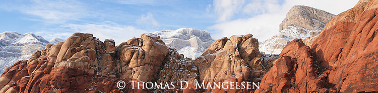 Snow dusts the variegated reds of the Aztec sandstone of the Calico Hills contrasting with the blue sky brushed with wispy clouds in the Red Rock Canyon National Conservation Area in Nevada.