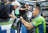 Clint Dempsey autographs a scarf after being introduced as a Sounder before a game against the Sounders FC and FC Dallas at CenturyLink Field in Seattle Saturday August, 3, 2013. The Sounders defeated Dallas 3-0.
