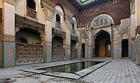 Low angle view of courtyard,  Sahrij Medersa (Medersa des Andalous), 1321, Fez, Morocco, pictured on February 21, 2009 in the morning. The Sahrij Medersa takes its name from the pool in its courtyard, (sahrij means basin). Green and white minarets crown the theological school founded by Merinid sultan Abou al-Hassan and attached to the Al-Andalous mosque.  It is decorated with ornate  dark cedar panels (mashrabiya), decorated tiles (zellij), marble pavings and intricate plasterwork. Fez, Morocco's second largest city, and one of the four imperial cities, was founded in 789 by Idris I on the banks of the River Fez. The oldest university in the world is here and the city is still the Moroccan cultural and spiritual centre. Fez has three sectors: the oldest part, the walled city of Fes-el-Bali, houses Morocco's largest medina and is a UNESCO World Heritage Site;  Fes-el-Jedid was founded in 1244 as a new capital by the Merenid dynasty, and contains the Mellah, or Jewish quarter; Ville Nouvelle was built by the French who took over most of Morocco in 1912 and transferred the capital to Rabat. Picture by Manuel Cohen.