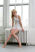 Blonde woman sitting on radiator looking at camera