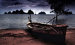 A Thai wooden fishing boat beached on an island in Phang Nga bay, Thailand.