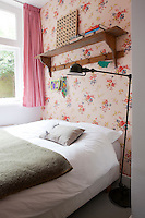 A chintz wallpaper by Cath Kidston teamed with an antique coat rack adds a touch of old fashioned  romance to this compact bedroom