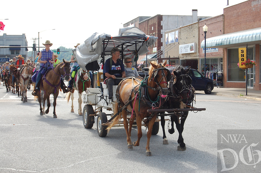 The John Henry Shaddox Wagon Train passes through downtown Harrison on Friday morning. This is the 37th year for the wagon train, which travels 71 miles over six days to arrive in Springdale just in time for the Rodeo of the Ozarks parade on Wednesday. Photo by Bill Bowden