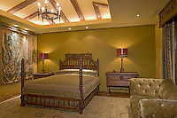 Ornate carved king size bed in elegant bedroom with green walls and domed wood beamed ceiling