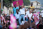 Singer Wyclef Jean and Haitian presidential candidates Michel Martelly and Charles Henry Baker (L-R) ride on top of a truck during an impromptu election protest on November 28, 2010 in Port-au-Prince, Haiti.
