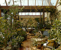 An antique chaise longue is situated in the midst of a luxuriant jungle of plants in this large conservatory