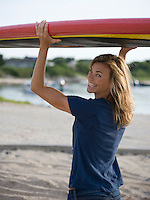 girl smiling  holding a paddleboard over her head