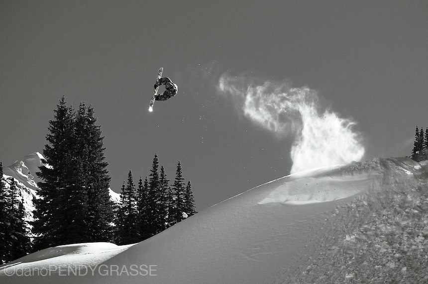 professional snowboarder romain de marchi leaves a trail of powder in ...