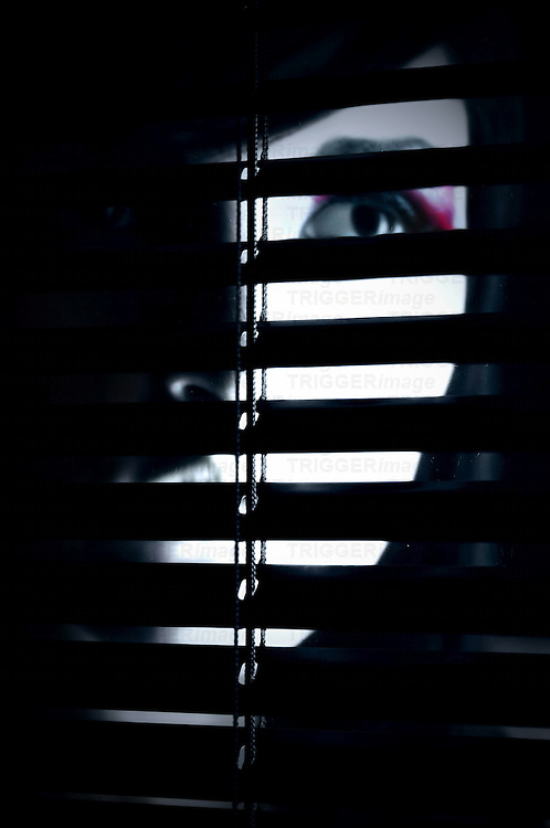 A partially hidden face of a young woman behind a screen