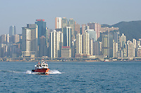 A pilot boat races through Hong Kong's Victoria harbour, in front of highrise apartment buildings at North Point glowing in the late afternoon sun