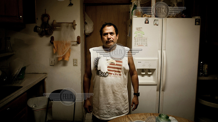 A Mexican migrant stands in his kitchen in Garden City, Kansas. He is one of the many people who have come to the town to work at the Tyson meat packing plant. This facility kills and processes between five and six thousand beef cattle every day. Kansas dominates the American beef industry, producing 25% of all beef raised in the USA. However, the industry is heavily dependent on cheap immigrant labour.