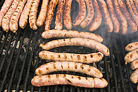 Barbecued sausages saucissons being cooked on griddle for sale as snack food at farmers market in Normandy, France